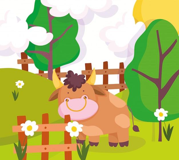 木製のフェンスの木の花の後ろに農場の動物の雄牛