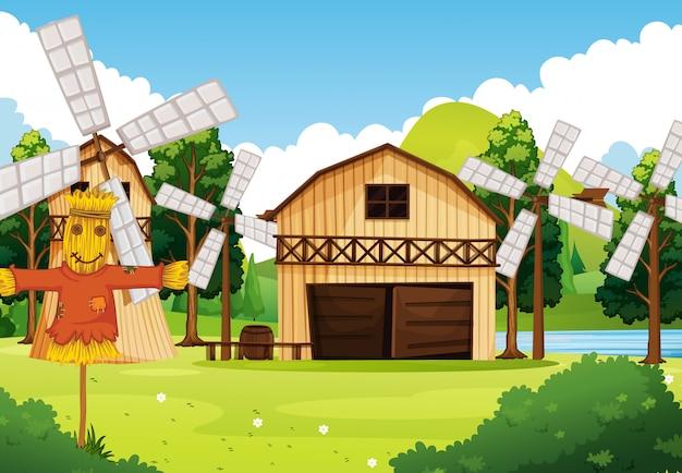 納屋と風車とかかしの自然シーンの農場
