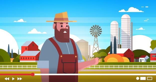 農家のブロガーがオンラインのビデオ男vloggerをユニフォームの近くの農場のブログのコンセプトフィールド農地の田舎の風景の肖像画の水平方向に記録