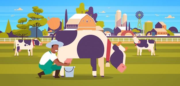 Фермер доения корова в ведро ферма домашнее животное крупный рогатый скот свежее молоко концепция горизонтальный сельскохозяйственные угодья сарай сельская местность пейзаж полная длина горизонтальный