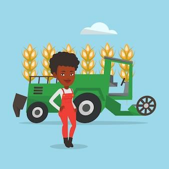 Фермер стоя с зернокомбайном на предпосылке.