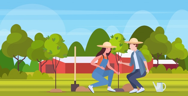 Farmers couple planting young tree gardeners woman man working in garden agricultural planting gardening eco farming concept farmland countryside landscape  full length horizontal