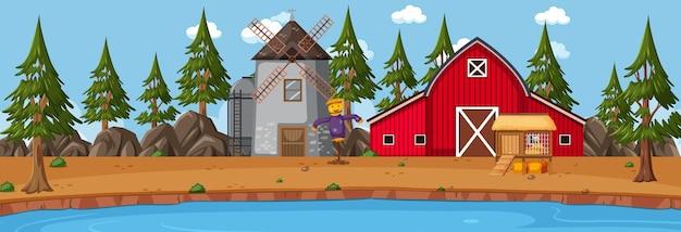 昼間の納屋と風車のある農地の水平方向のシーン