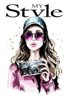 Женщина моды в кепке, держащей фотоаппарат