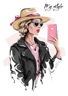 Женщина моды в шляпе, делая селфи