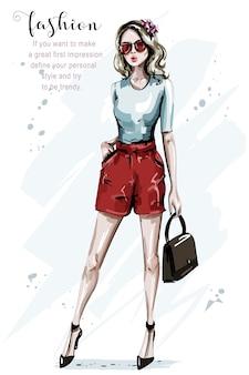 Женщина моды в красных шортах с очками и сумкой