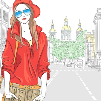 Модная привлекательная девушка в красной блузке, кепке и очках на улице в санкт-петербурге