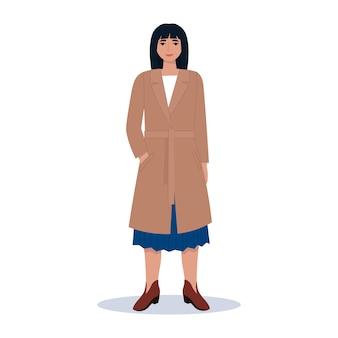 코트와 부츠에 유행 젊은 여자. 가을 거리 스타일의 옷.