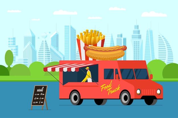 Красный грузовик быстрого питания с хот-догом в городском парке на открытом воздухе и картофелем фри на крыше фургона, зажаренным с хрустящей корочкой