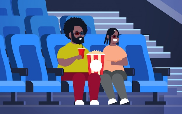 Fat couple in 3d glasses watching movie sitting in cinema with popcorn and cola overweight african american man woman having date and laughing at new comedy flat full length horizontal