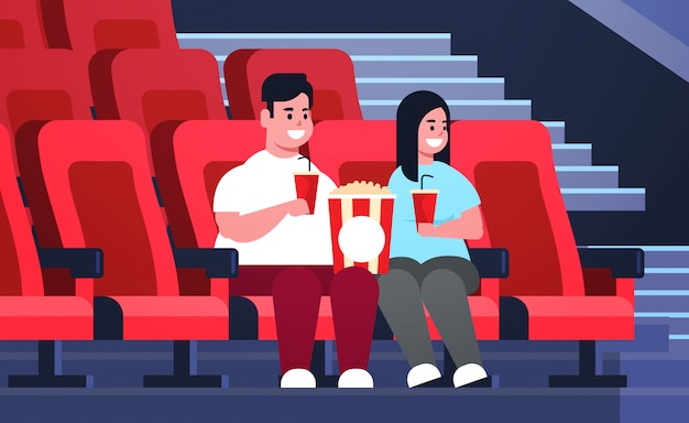 Fat couple watching movie sitting in cinema with popcorn and cola overweight man woman having date and laughing at new comedy flat full length horizontal
