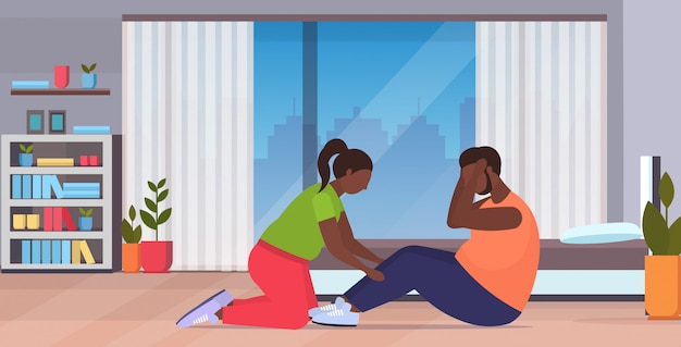 Fat man doing sit-ups exercises with overweight woman holding his legs couple training together workout weight loss concept modern living room interior full length horizontal