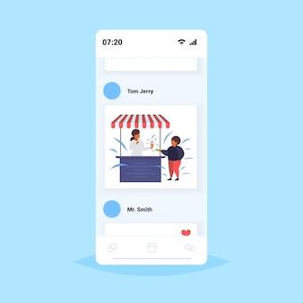 脂肪の肥満の少年が屋台でアイスクリームを買う不健康な栄養肥満の概念アフリカ系アメリカ人の男が楽しんでいるスマートフォン画面オンラインモバイルアプリ
