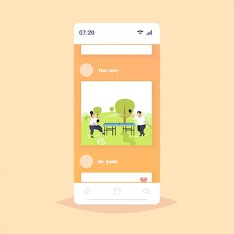 太った肥満のカップルがピンポン卓球を再生します太りすぎの男性女性公共の公園で屋外楽しんで減量の概念スマートフォンの画面オンラインモバイルアプリ