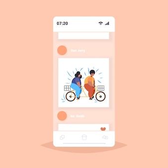 太った肥満のカップルがタンデム自転車に乗って太りすぎのアフリカ系アメリカ人男性女性サイクリングツインバイク減量コンセプトスマートフォン画面オンラインモバイルアプリ