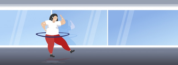 Fat obese girl twisting hula hoop overweight sweat woman cardio training workout weight loss concept  full length modern gym studio interior horizontal