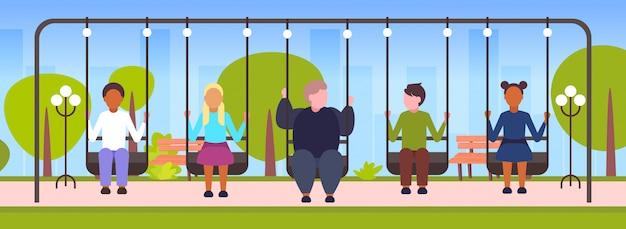 Толстый парень парень качается с микс гонки друзья ожирение концепция люди сидят на качелях весело открытый пейзаж фон полная длина горизонтальный