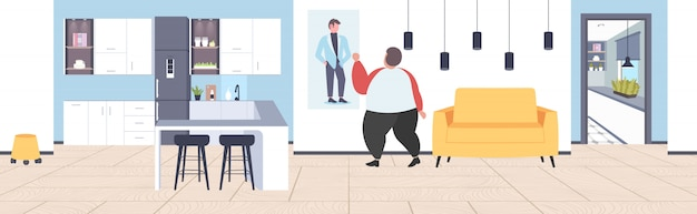 Fat obese man looking at thin guy on picture weight loss motivation obesity concept modern home apartment interior
