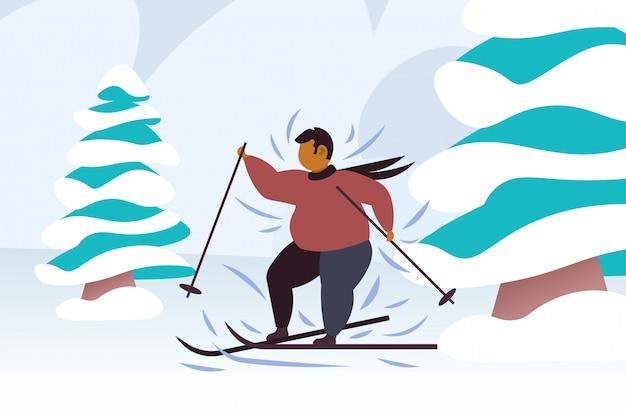 겨울 시즌 과체중 남자 스키 체중 감량 개념 눈 덮인 언덕 전나무 나무 숲 풍경에 활성 레저를 수행하는 뚱뚱한 비만 남자 스키