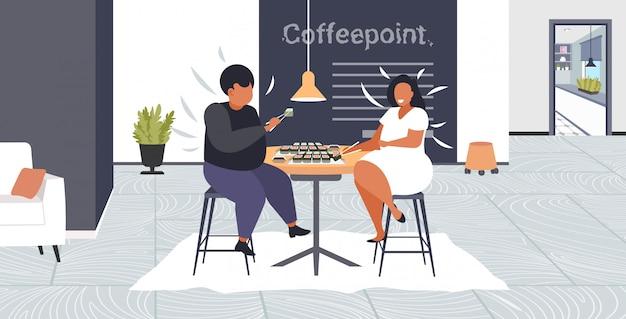 Толстый тучный мужчина женщина ест суши избыточный вес пара сидит за столом кафе с обедом ожирение нездоровое питание концепция современный кофе точка интерьер
