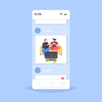 Толстый мужчина мужчина сидит на диване с помощью джойстика игровой коврик избыточный вес пара курсирует видеоигры на тв ожирение нездоровый образ жизни концепция смартфон экран онлайн мобильное приложение полная длина