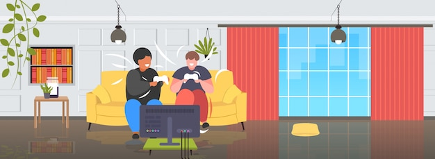 Fat obese men sitting on couch using joystick game pad overweight mix race couple plying video games on tv obesity unhealthy lifestyle concept modern living room interior full length horizontal