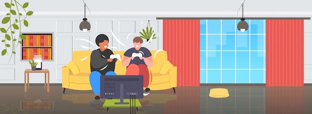 Толстые мужчины, сидящие на диване, с помощью джойстика, геймпад, избыточный вес, микс, гонка, пара, курсирующие видеоигры, по телевизору, ожирение, нездоровый образ жизни, концепция, современная гостиная, интерьер, горизонтальный, полная длина
