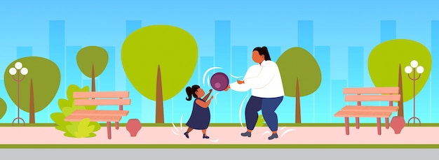 Fat obese mother with daughter playing with ball outdoor overweight woman and child having fun together weight loss physical activity concept urban park cityscape background  full length