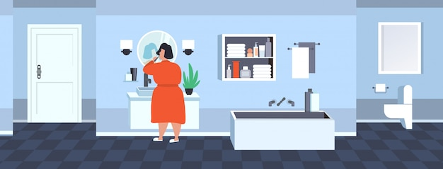 Fat obese woman brushing teeth overweight african american girl holding toothbrush looking at mirror obesity concept modern bathroom interior  full length rear view horizontal