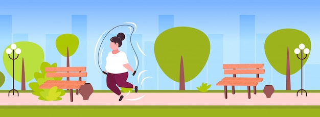 Fat obese woman doing exercises with jumping rope overweight girl cardio training workout weight loss concept summer park landscape