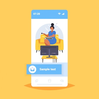 Tv 비만 건강에 해로운 영양 개념 스마트 폰 화면 온라인 모바일 앱을보고 안락의 자에 앉아 초밥 비만 소녀를 먹는 뚱뚱한 비만 여성