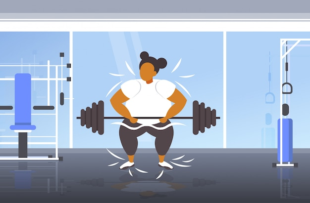 Fat obese woman lifting barbell overweight african american girl cardio training workout weight loss concept modern gym interior