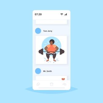 脂肪肥満の女性がバーベルを持ち上げる太りすぎのアフリカ系アメリカ人の女の子トレーニングトレーニング減量の概念スマートフォンスクリーンオンラインモバイルアプリ
