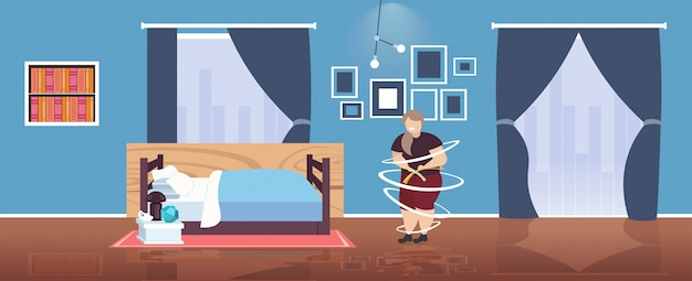 Fat obese woman measuring her waistline sad overweight girl using tape measure weight loss obesity concept modern bedroom interior  full length horizontal