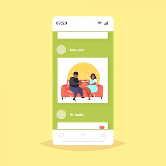 Fat overweight couple giving surprises gift boxes to each other obese mix race man woman sitting on couch holiday celebration obesity concept smartphone screen online mobile app