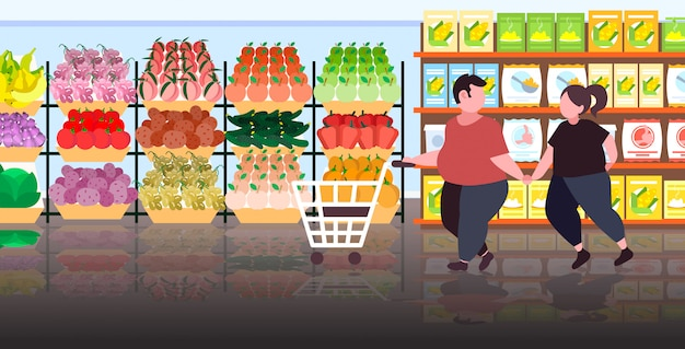 脂肪肥満カップルトロリーカートを押して肥満男性女性が食料品店で野菜や果物を購入健康的な栄養減量コンセプトモダンなスーパーマーケットのインテリア