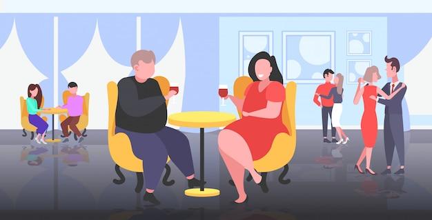 カフェで座っている太りすぎの肥満カップルテーブル肥満の男性女性ワインを飲む不健康なライフスタイル肥満の概念人々が楽しんでモダンなレストラン
