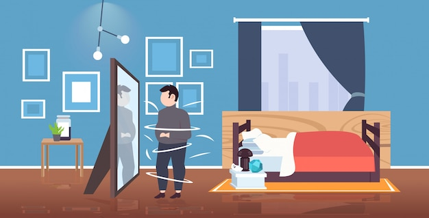 Fat overweight man looking at reflection in mirror sad obese guy unhealthy lifestyle obesity concept modern bedroom interior horizontal  full length