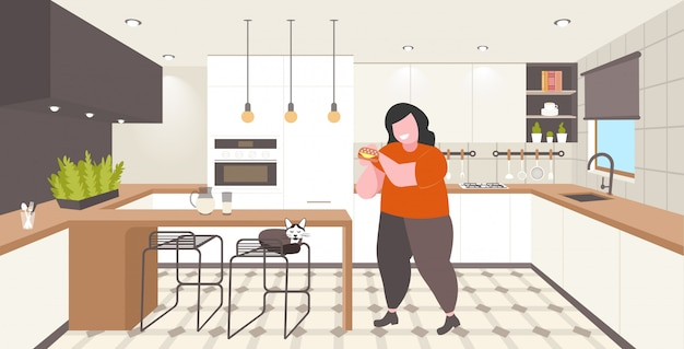 Fat overweight woman eating hamburger obesity unhealthy nutrition fast food concept obese girl having lunch modern kitchen interior horizontal full length