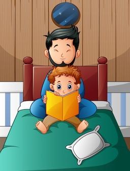 Отец и его сын читают книгу в постели ночью