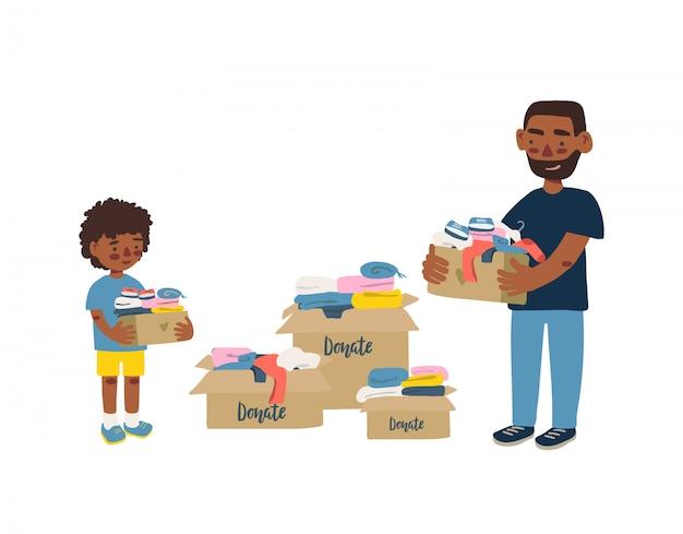 寄付やリサイクルのための衣類が入った段ボール箱を抱える父と息子。