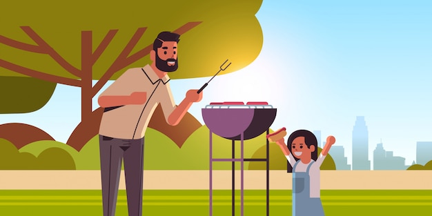 Father and daughter preparing hot dogs on grill happy family having fun picnic barbecue party concept summer park landscape background flat portrait horizontal