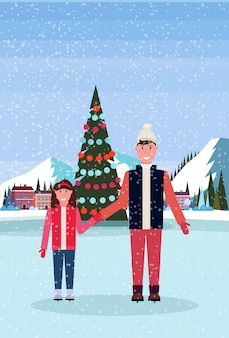 Father and daughter skating in ice rink with decorated christmas tree at ski resort hotel