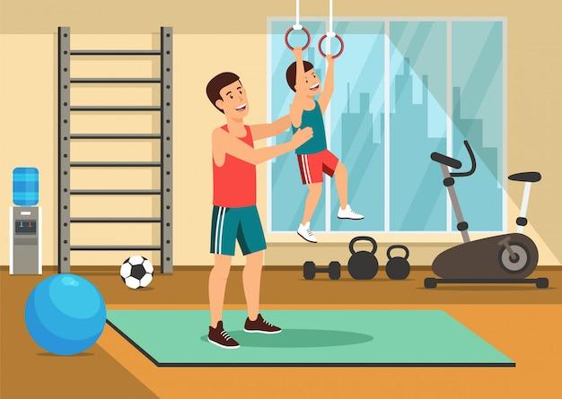 Отец помогает сыну подтянуться на гимнастическом кольце