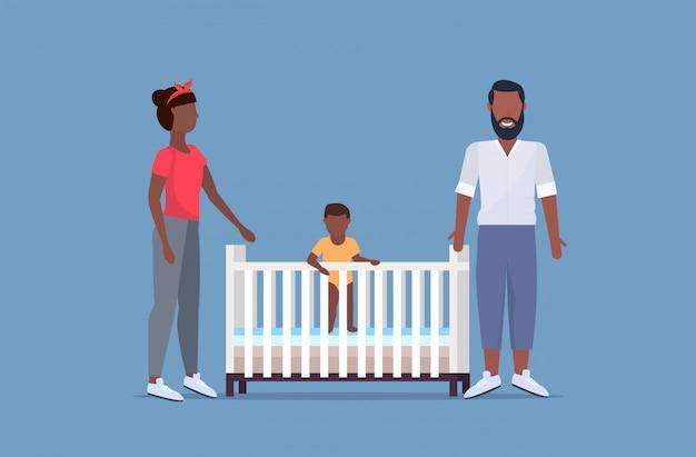 Отец мать и их новорожденный ребенок в кроватке веселились вместе счастливая семья концепция родителей родители стояли маленький ребенок полная длина горизонтальный