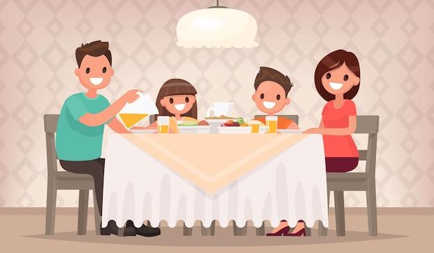 Отец, мать, сын и дочь вместе сидят за столом и обедают