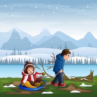 Father pulling his son riding on a sled