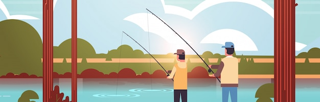 Father and son fishing together rear view man with little boy using rods happy family weekend fisher hobby concept sunset mountains landscape background flat portrait horizontal