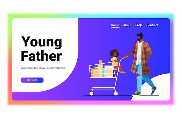 슈퍼마켓 아버지가 육아 쇼핑 개념 가로에서 식료품을 사는 트롤리 카트에 작은 딸과 함께 아버지