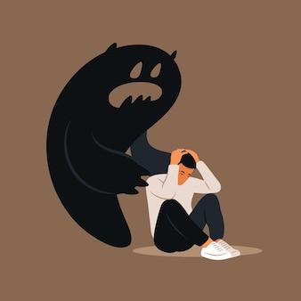 Страх или паническая атака. печальный человек с опущенной головой напуган собственной тенью. понятие депрессии, одиночества, беспокойства.
